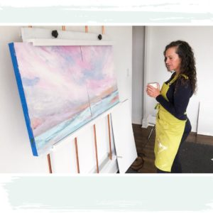 Lisa Mann holding coffee cup and contemplating a painting she is working on