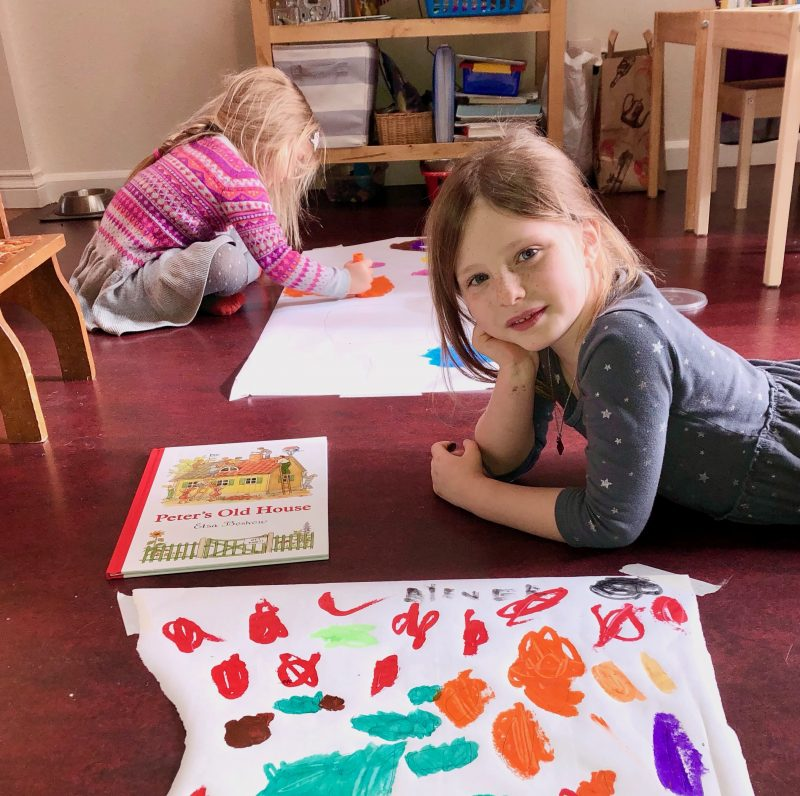 children painting and one looking at the camera